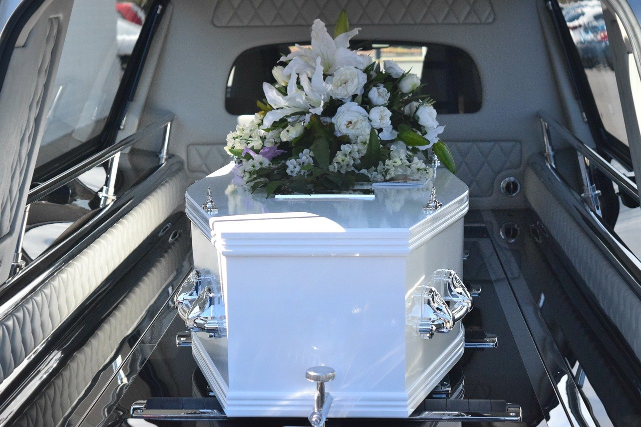 image of a white coffin inside a funeral vehicle