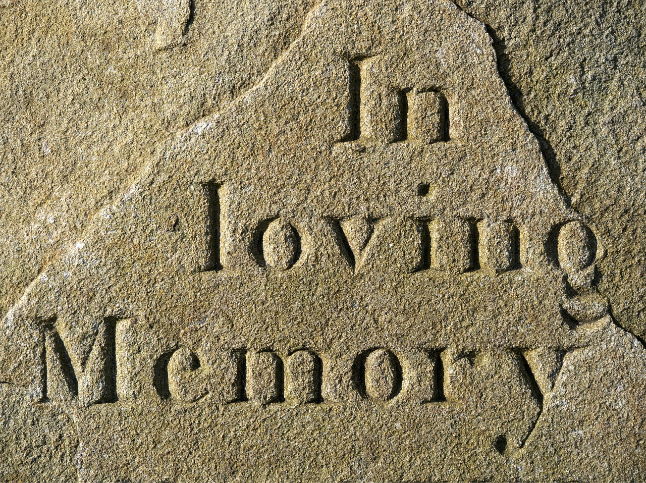 """Image of headstone with """"In loving memory"""" inscription"""